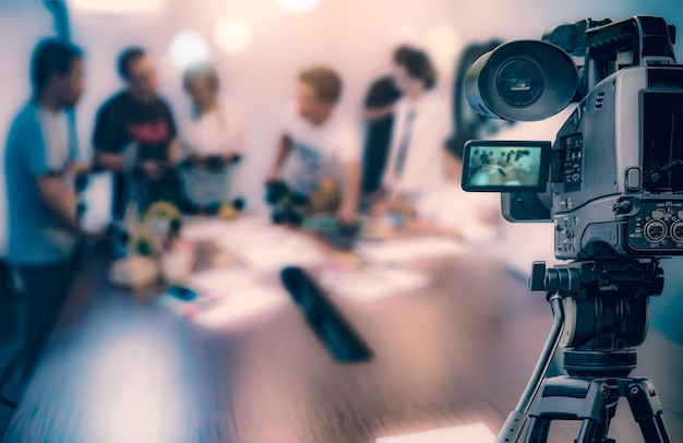 Video camera taking live video streaming at people working background Premium Photo