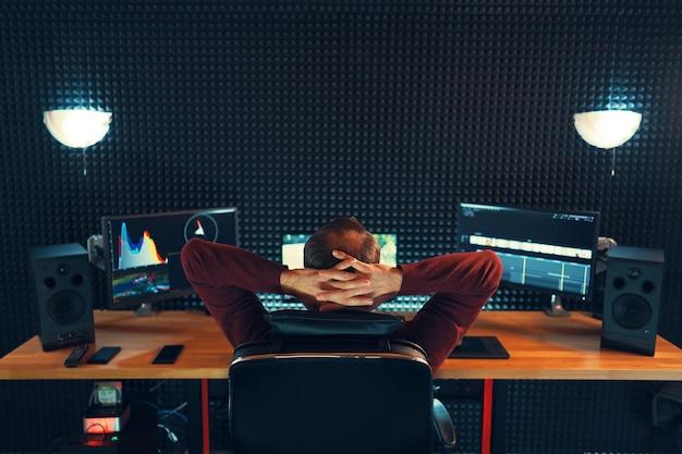 Редактирование видео. профессиональный редактор, добавляющий специальные звуковые эффекты. вид сзади молодого человека, наблюдающего за графиками на мониторах. скопируйте пространство на серой стене Premium Фотографии