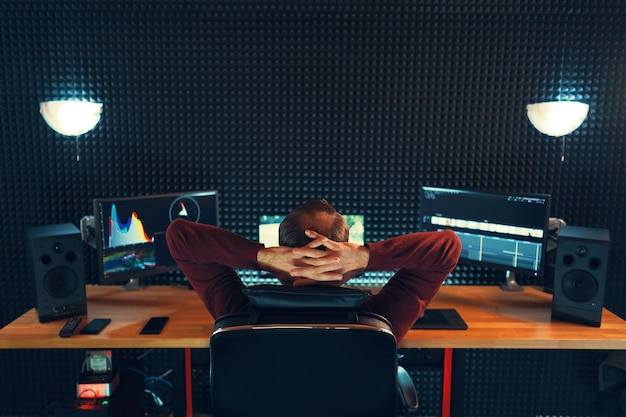 Video editing. professional editor adding special sound effects. back view of young man watching graphs on monitors. copy space on gray wall Premium Photo