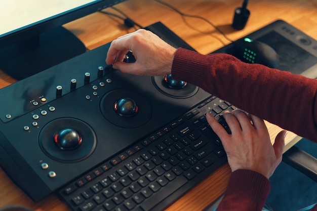 Video editor hands adjusting color or sound on working console m Premium Photo