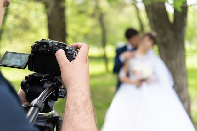 The videographer shootes the marrieds in the garden in the summer. Premium Photo