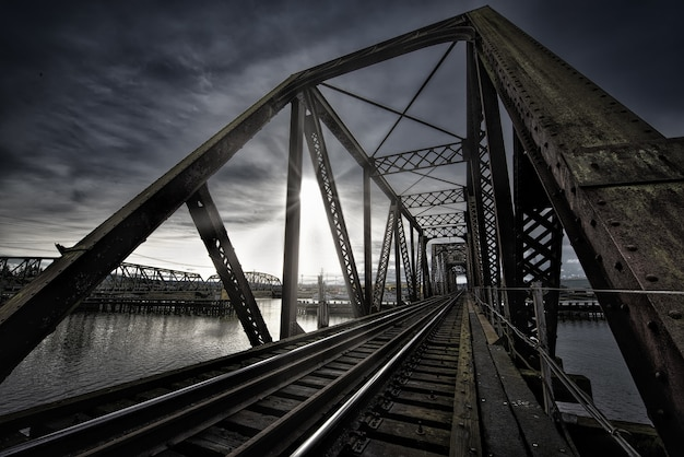 Vierendeel bridge with train track near the lake and the breathtaking sun shining in the dark sky Free Photo