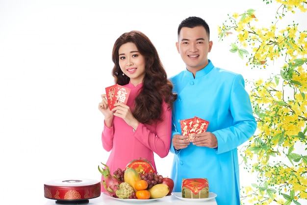Vietnamese couple posing in studio with blooming mimosa and traditional new year attributes Free Photo