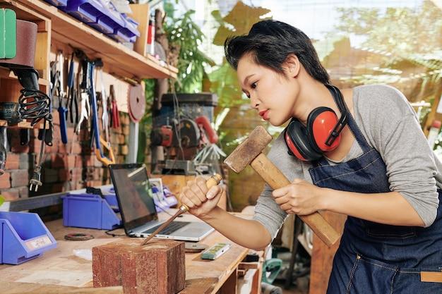 Вьетнамская женщина-плотник использует долото и молоток при работе с твердой древесиной Premium Фотографии