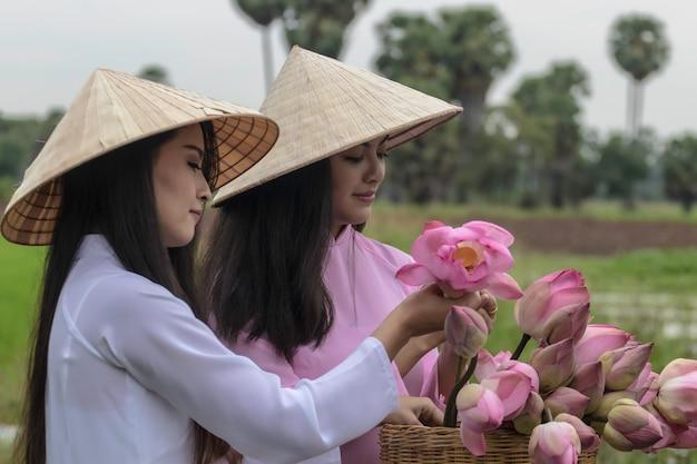 Vietnamese girls wearing national dress and folding lotus flowers on a bicycle. Premium Photo