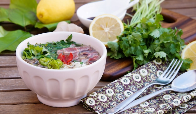 Vietnamese noodle soup with broth, linguine-shaped rice noodles, cilantro and beef Premium Photo