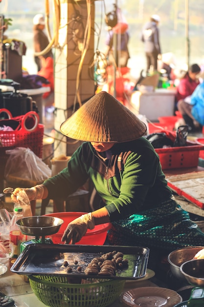 Vietnamese woman selling food on a roadside market in hoi an, quang nam province, vietnam. Premium Photo