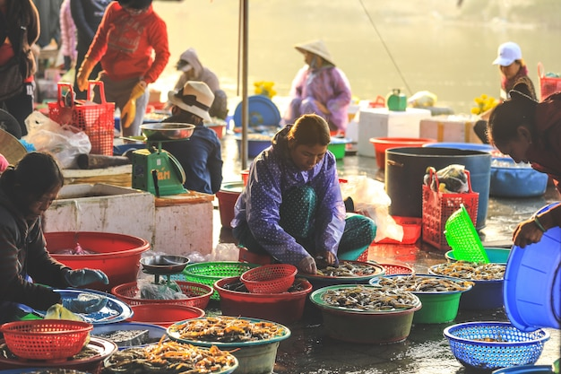 Vietnamese woman selling seafood from large bowls at a roadside market in hoi an, quang nam province Premium Photo