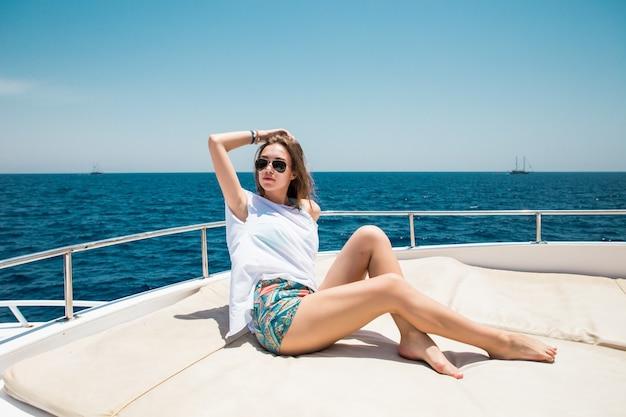 Вид на молодую привлекательную женщину, расслабляющуюся на роскошной яхте, плавающей в синем море Бесплатные Фотографии