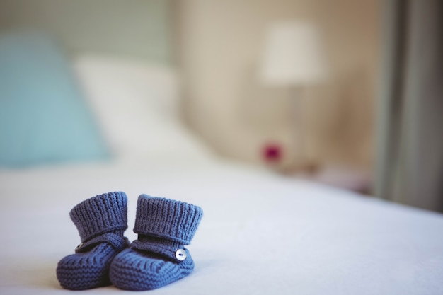View of baby shoes on a bed at home Premium Photo