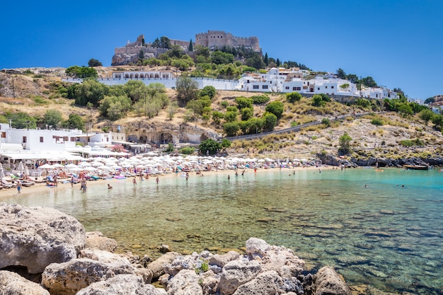 View of the beach ant the fortress in lindos town. rhodes, greece Premium Photo