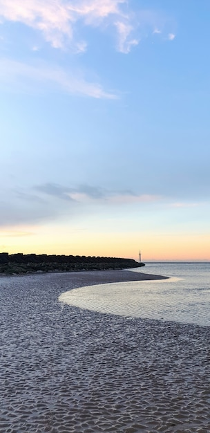 View of the beach in liverpool at sunset, rows of breakwaters, united kingdom Free Photo
