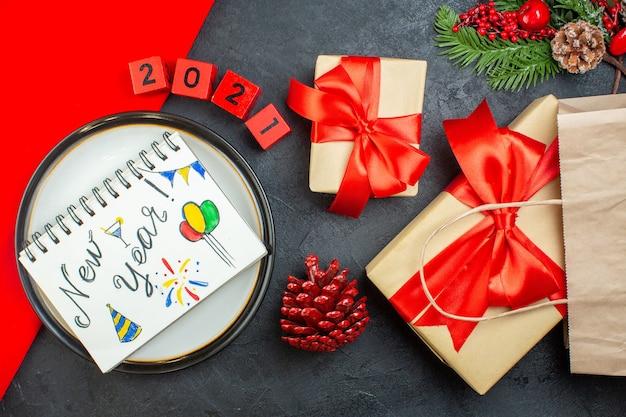 Sopra la vista di bellissimi regali e taccuino con disegni di capodanno su un piatto cono cono di rami di abete numeri su un tavolo scuro Foto Gratuite
