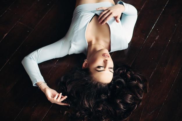 Above view of beautiful woman in blue dress lying on dark wooden floor. Premium Photo