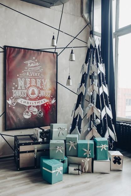 Vista sulla tavola rotonda splendidamente decorata con rami di abete naturale, candela, due flauti, piatti contro il divano classico in un appartamento moderno. Foto Gratuite