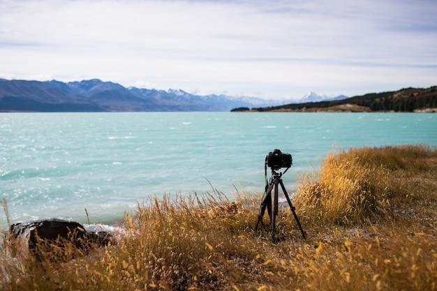 Vista di una telecamera su uno stand vicino al bellissimo lago e le colline all'orizzonte in una giornata di sole Foto Gratuite