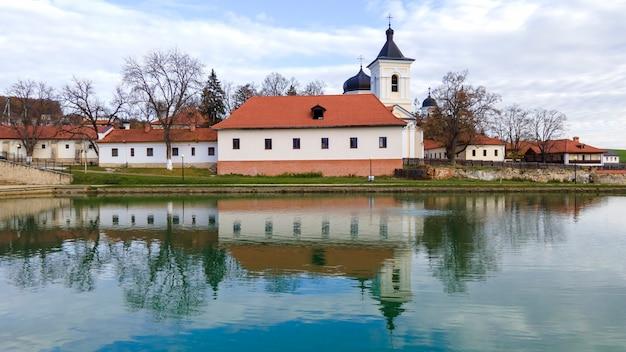 Veduta del monastero di capriana. la chiesa di pietra, gli edifici, gli alberi spogli. un lago in primo piano, bel tempo in moldova Foto Gratuite