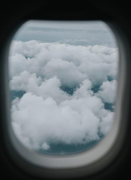 Vista di un cielo nuvoloso attraverso il finestrino di un aeroplano Foto Gratuite