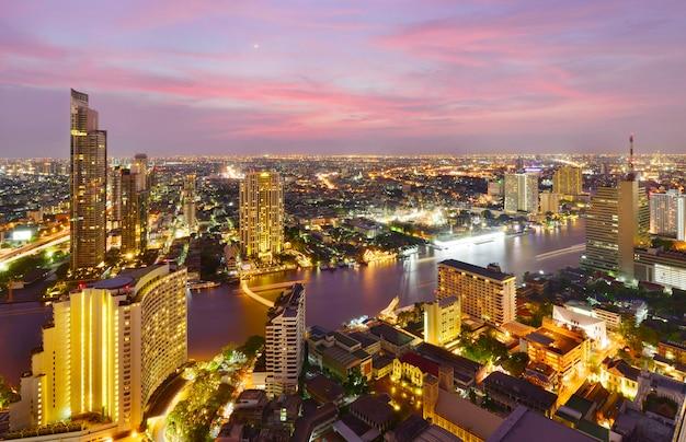 Посмотреть коммерческое современное здание и реку чао прайя в центре города в сумерках в бангкоке, таиланд Premium Фотографии