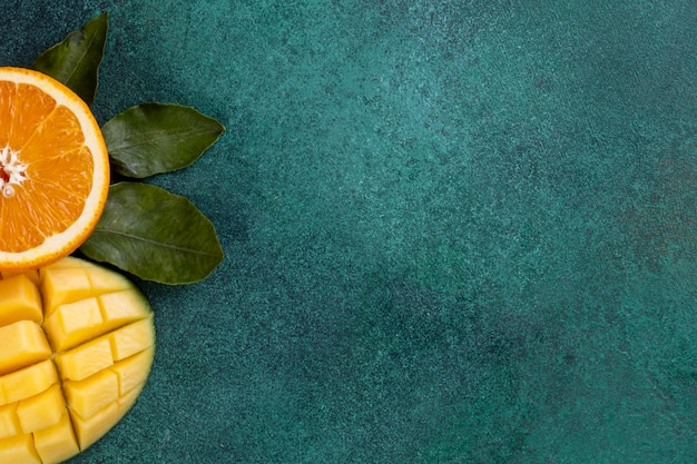 View  copy space  sliced mango with half an orange on a green table Free Photo