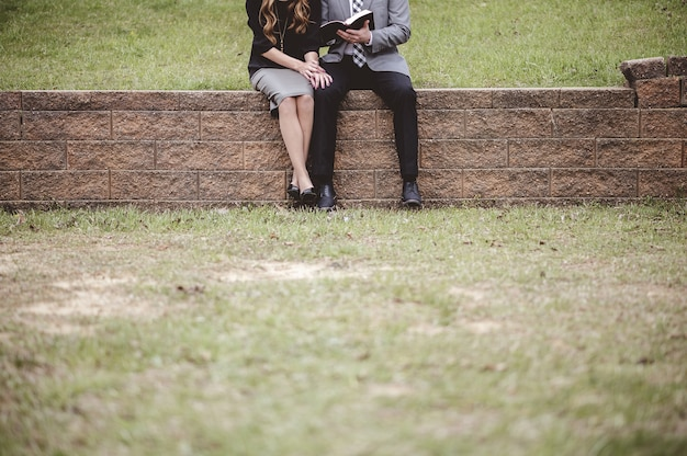 View of a couple wearing formal clothes, reading and discussing a book while sitting in a garden Free Photo