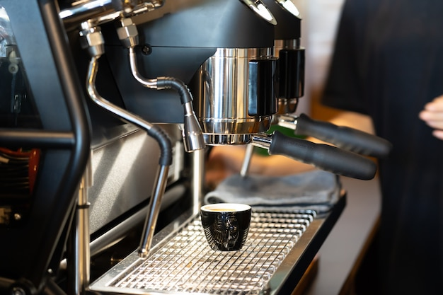 View of cup of coffee under coffee grinder. Premium Photo