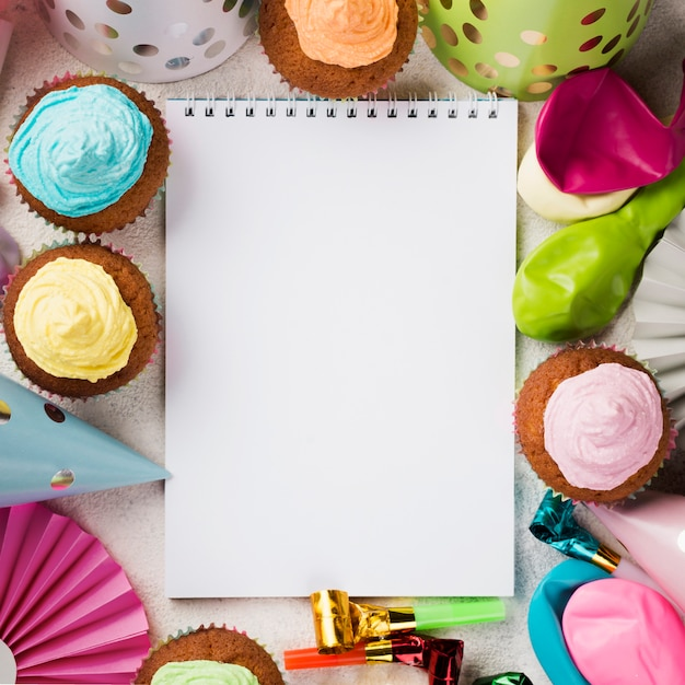 Above view decoration with notebook and muffins Free Photo