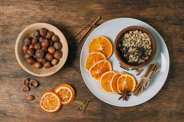 Above view decoration with orange slices and hazelnuts Free Photo