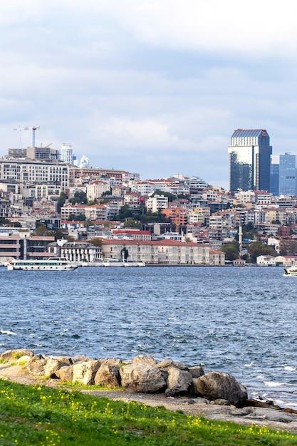 Vista di un quartiere residenziale e alto e moderno di istanbul, lo stretto del bosforo con barche, persone in appoggio sulla riva, turchia Foto Gratuite