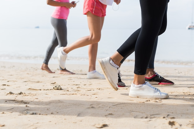 View of feet running on beach together Premium Photo
