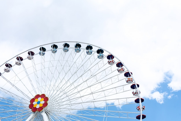 View of the ferris wheel against the background of blue sky and white clouds. Premium Photo