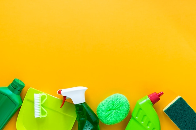 Above view frame with cleaning products on yellow background Free Photo