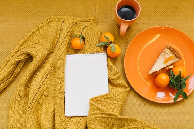上から見るオレンジセーター、マンダリン、チーズケーキ、一杯のコーヒー、オレンジ色のテーブルに白いノート 無料写真