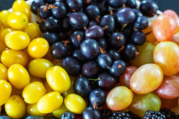 上からの眺め。ホワイトテレルの果実のミックス。三角形の分離。果物の夏ミックス。ベリーのスタイリッシュなレイアウト Premium写真