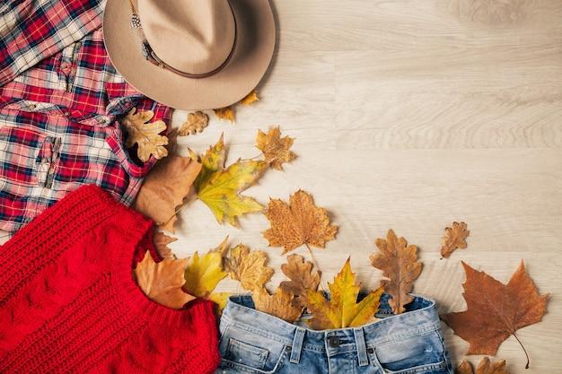 Вид сверху на плоскую планировку женского стиля и аксессуаров, красный вязаный свитер, клетчатую фланелевую рубашку, джинсовые джинсы, шляпу, осеннюю тенденцию моды, вид сверху, одежда, желтые листья Бесплатные Фотографии