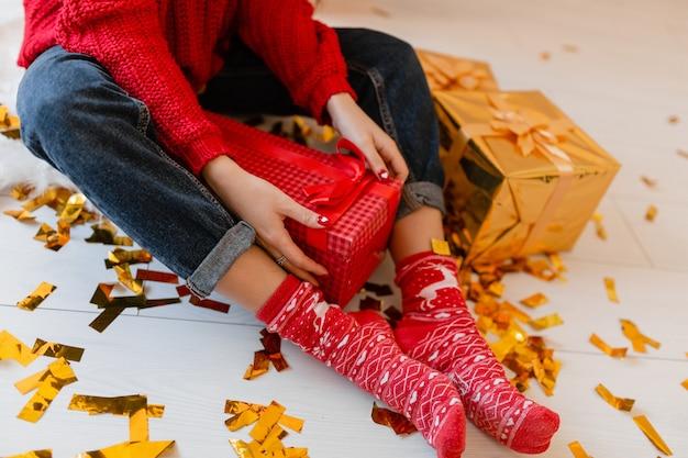 Peresents 및 선물 상자를 풀고 황금 색종이에 크리스마스에 집에 앉아 빨간 양말에 여자 위에서보기 무료 사진