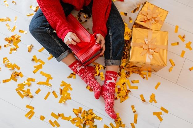 Вид сверху на женщину в красных носках, сидящую дома на рождество на золотом конфетти, распаковывающую подарки и подарочные коробки Бесплатные Фотографии