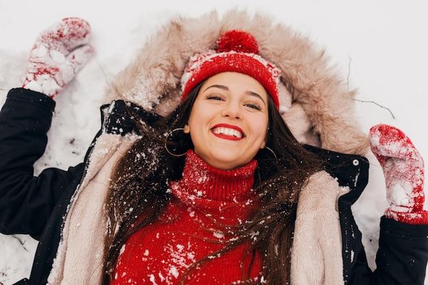 公園で雪の中で横たわっている黒いコートを着て、暖かい服を着て、楽しんで、赤いミトンとニット帽の若いかなり率直な笑顔の幸せな女性を上から見る 無料写真