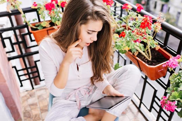 朝のバルコニーでパジャマで長い髪のかなり若い女の子を上から表示します。彼女はタブレットで読んでびっくりしました。 無料写真
