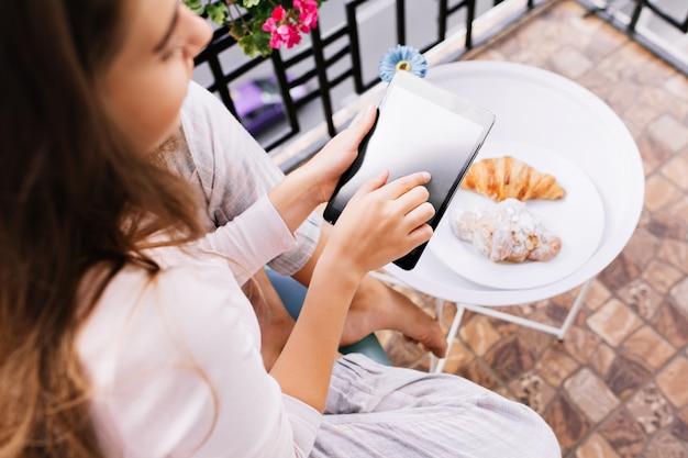 朝は朝食をとり、バルコニーに座っているパジャマの女の子の手でタブレットの上からの眺め。 無料写真