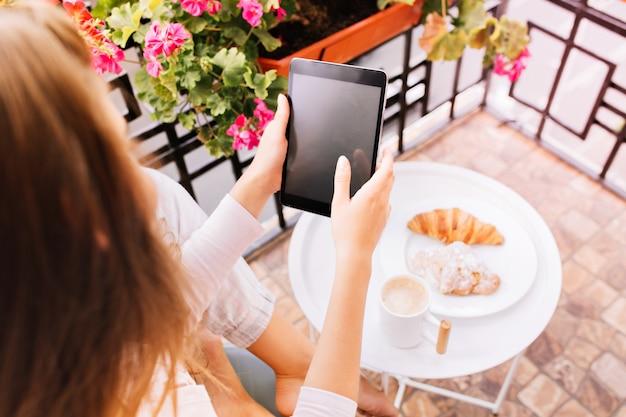 朝は朝食をとり、バルコニーに座っているパジャマの女の子の手でタブレットの上からタブレットを見る。 無料写真