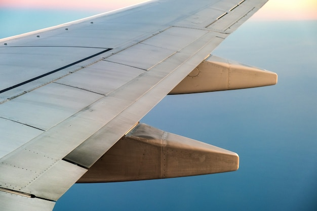 View from airplane on the aircraft white wing flying over ocean landscape in sunny morning Premium Photo