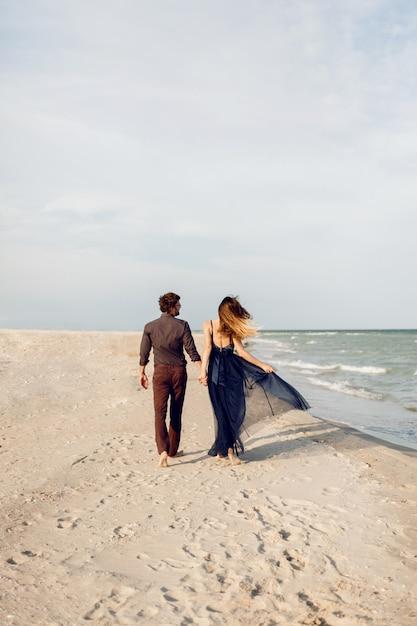 後ろから見たところ。ビーチに沿って歩く愛のエレガントなカップル。ロマンチックな瞬間。白い砂浜と海の波。熱帯の休暇。全高。 無料写真