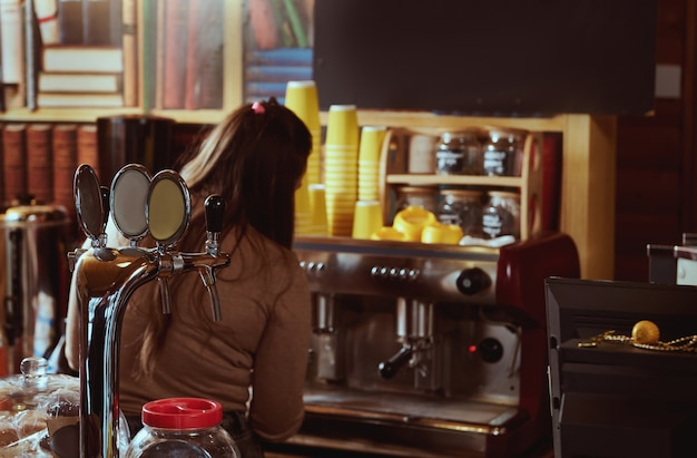 View from the back of female barista preparing coffee in professional coffee machine Premium Photo