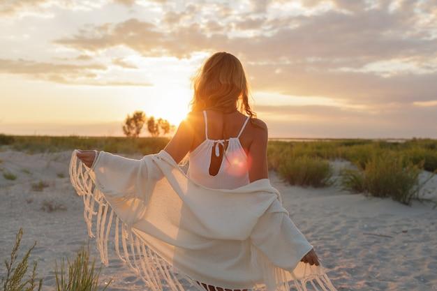 Vista dal retro della graziosa donna dello zenzero che gode del tramonto incredibile sulla spiaggia. Foto Gratuite