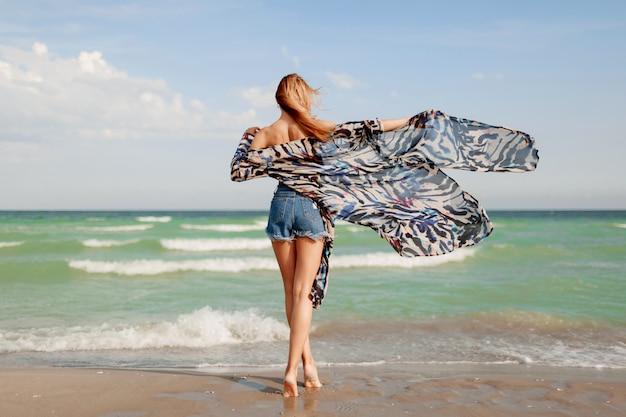 Вид со спины стройной загорелой рыжеволосой девушки в стильном тропическом наряде, позирующей на потрясающем пляже у океана Бесплатные Фотографии