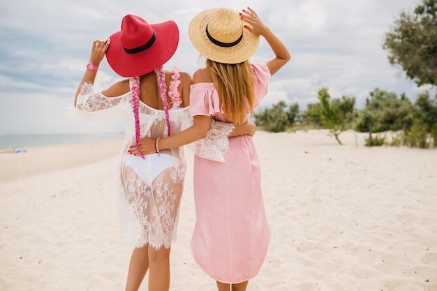 Вид сзади на двух красивых стильных женщин на пляже в отпуске, летний стиль, модная тенденция, в соломенных шляпах, модная тенденция, розовое и кружевное платье, сексуальный наряд Бесплатные Фотографии