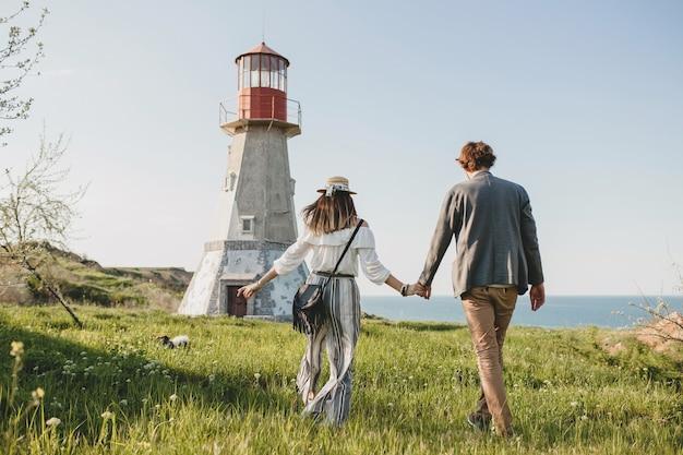 Вид сзади на молодую пару битник в стиле инди в любви, гуляющую в сельской местности, держась за руки, маяк на заднем плане, теплый летний день, солнечный, богемный наряд, шляпа Бесплатные Фотографии