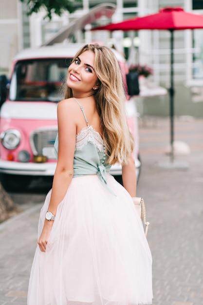 Вид со спины булавки в стиле девушки с длинными светлыми волосами, идущей по улице. она улыбается в камеру. Бесплатные Фотографии