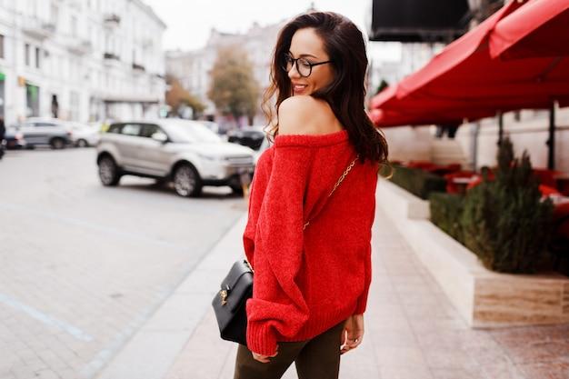 Вид со спины. уличный модный образ симпатичной брюнетки в модном красном свитере, весенняя прогулка по улице. Бесплатные Фотографии